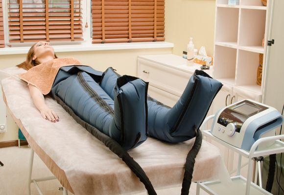 девушка лежит в костюме для прессотерапии
