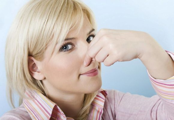 девушка закрывает нос пальцами